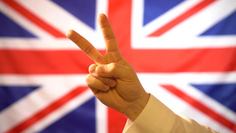 United Kingdom shows two fingers, a gesture of peace on the background of the Live Action