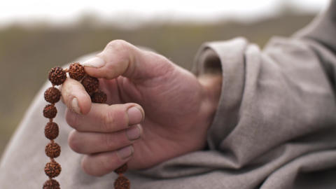 Man meditating with beads on nature Live Action