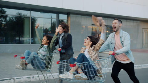 Group of friends students having fun in city riding shopping trolleys laughing Live Action