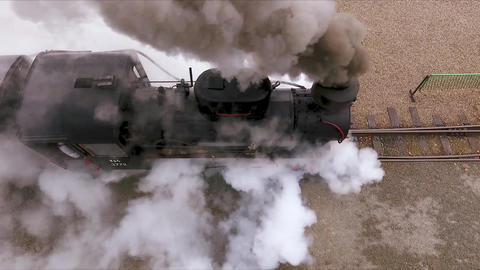 Aerial view from above of old locomotive moving through railway, producing smoke Live Action