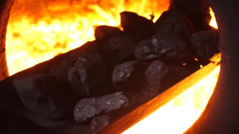 Throwing coals with shovel into the furnace Acción en vivo