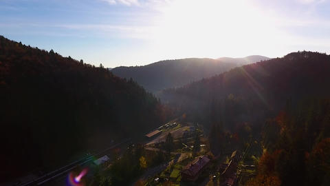 Beautiful mountains at sunset, autumn forest valley panoramic view from drone, village with railway Live Action