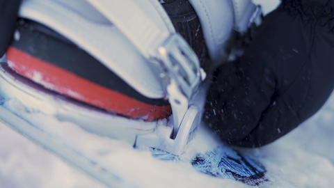 Close up of a girl fastening snowboard boots. Mounting bindings Live Action