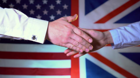 The concept of cooperation between countries. USA and Great Britain handshake Live Action
