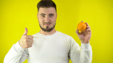 A young man holds a fresh orange in his hand. A man in a white sweatshirt shows Live Action