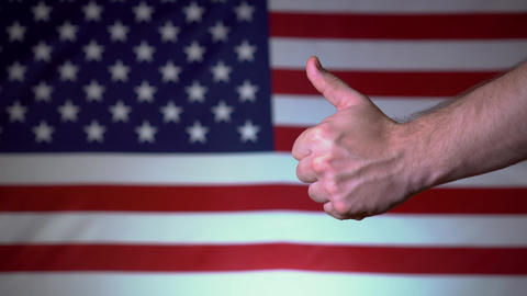 Against the backdrop of the American flag, the hand shows a thumb up. US Live Action