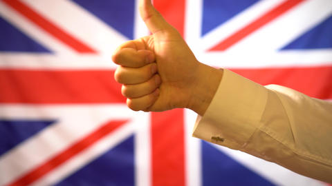 Against the backdrop of the UK flag, the hand shows a thumb up. UK approval Live Action