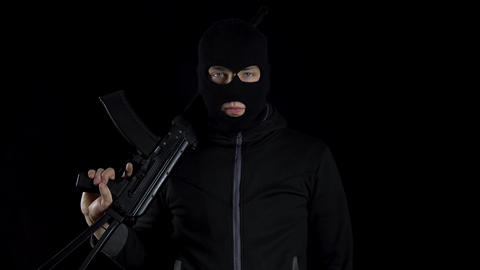 A man in a balaclava mask stands with an AK-47 assault rifle. A bandit stands Live Action