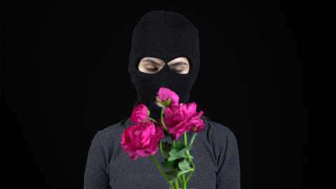 A woman in a balaclava mask is standing with flowers. The thug discards a Live Action