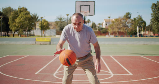 Old man play on basketball court Live Action