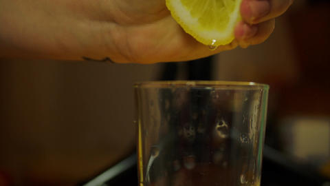 Woman Hand Squeezing Half A Lemon For Juice In A Tall Glass Footage