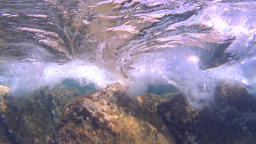 Underwater, waves splashing over the rocks, slow motion Footage