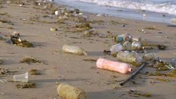 Plastic bottles littering the coast line of a deserted beach and in the ocean Footage