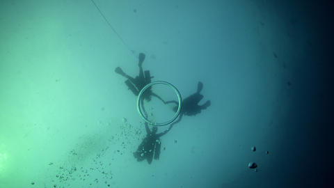 SCUBA divers in formation over bubble ring Live Action