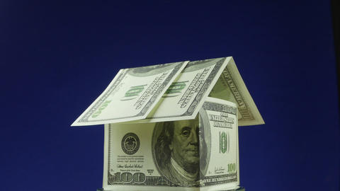 House of hundred dollar bills on a blue background. Chromakey Live Action