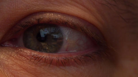 Mans Eye looks at the computer screen. The screen is reflected in the eye Live Action