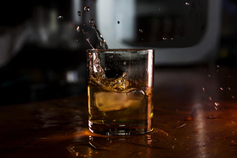 Whiskey With Ice Served in a Bar and Splashes out of Glass Fotografía