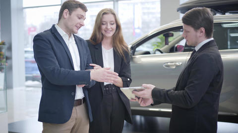 Young Caucasian successful couple selecting new vehicle in car dealership Live Action
