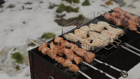 The process of cooking barbecue on fire in winter weather on a background of Live Action