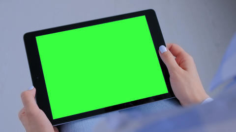 Woman using black tablet computer with blank green screen - copy space concept Live Action
