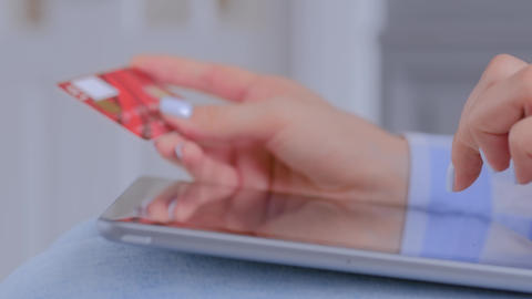 Woman using tablet device and credit card for online shopping - close up view Live Action
