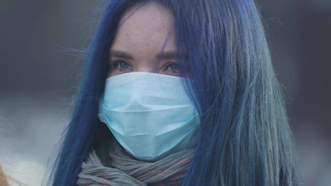 Close-up face of young woman with blue hair and blue eyes wearing protective Live Action