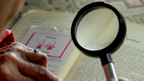 Very Old Lady Reading A Book With A Magnifying Glass, Over The Shoulder Shot Footage