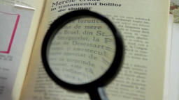 Detail Of Magnifying Glass Used For Reading A Book, Rack Focus Footage