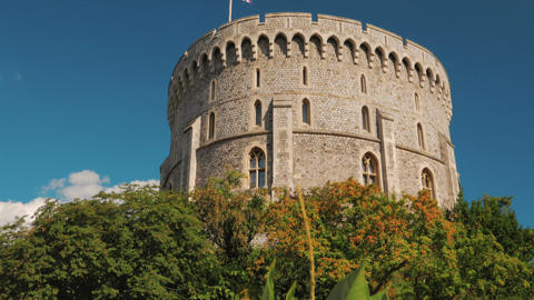 Closeup Shot of a Windsor Castle Tower Framed by Vegetation and the Union Jack F Footage