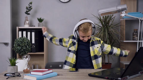 Portrait of attractive cheerful funny teen boy in headphones which enjoying Live Action