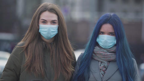 Two young women in protective masks looking at each other, signing and looking Live Action
