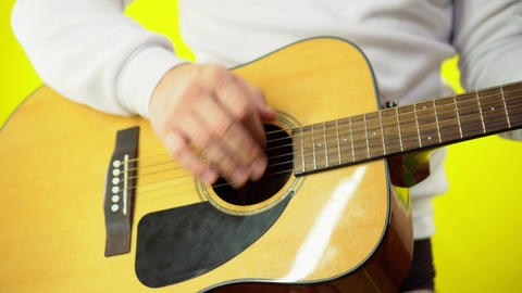 Close-up of a man's hand playing the guitar. Hand of a man in a white sweatshirt Live Action