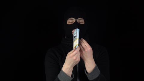 A man in a balaclava mask is standing with a bundle of dollars. The thug leafing Live Action