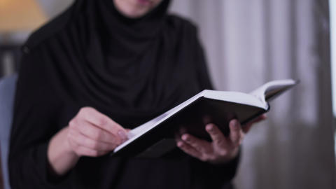 Close-up of book in female Muslim hands. Blurred woman in traditional black Live Action