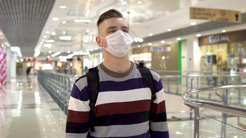 A young man in a medical mask walks in a shopping center. The man is coughing Live Action