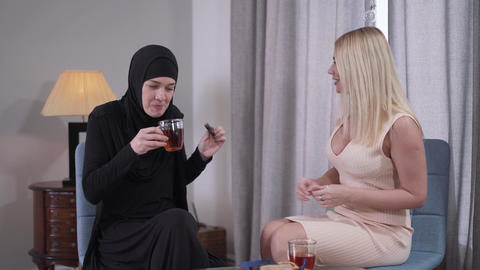 Positive Muslim woman in traditional black hijab drinking tea with Caucasian Live Action