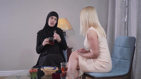 Young Muslim woman in traditional outfit talking with Caucasian blond female Live Action