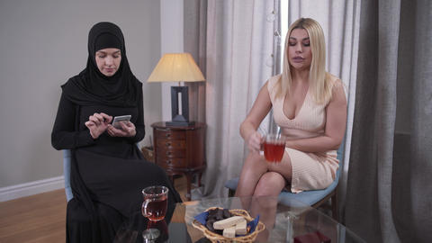 Young blond Caucasian woman in candid dress looking at conservative Muslim woman Live Action