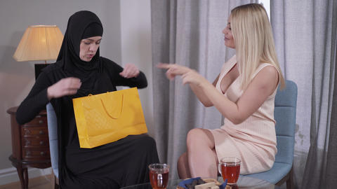 Conservative Muslim woman getting present from Caucasian modern friend. Young Live Action