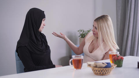 Modern confident Caucasian woman criticizing outfit of Muslim friend. Young lady Live Action