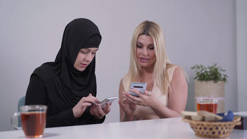 Two young women from different cultures using social media on smartphones Live Action