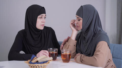 Modest Muslim woman in hijab calming down her modern-looking female friend Live Action
