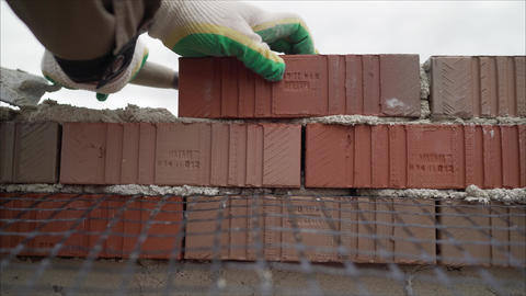 Laying of red bricks. Profesional worker builds an expensive red brick house Live Action