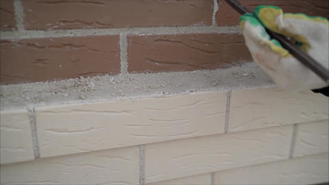 Worker wipes a wall brickwork. Worker wipes the seam between the bricks. Worker Live Action
