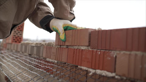 Worker builds a wall of red silicate brick.. Bricklayer build walls in Live Action