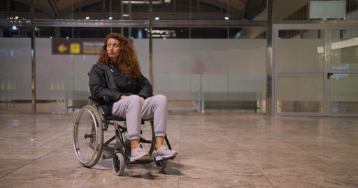 Young disabled woman in wheelchair in an airport. She is alone and looking Live Action
