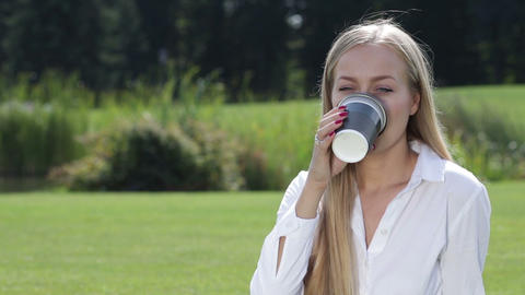Cheerful young woman drinking coffee outside Footage