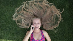 Woman with blonde amazing long hair lying on grass Footage