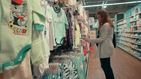 Woman Chooses Clothing for a Child Department Footage