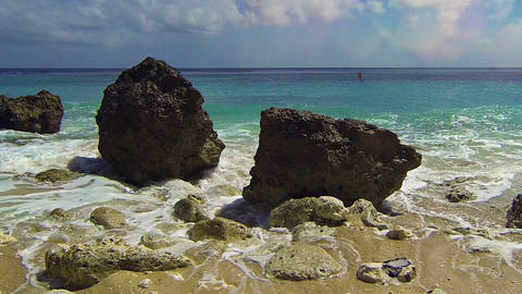Gentle Waves Wash over Boulders on a Tropical Beach Paradise. with Sound Footage